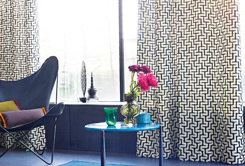Foto d'interni di un salotto con tavolino, poltrona e tenda del brand Zimmer+Rohde