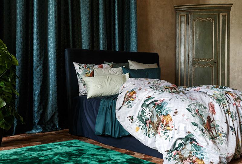 Foto di un letto decorato con cuscini e tessuti della linea camera da letto del brand Christian Fischbacher